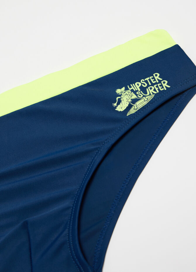 Solid colour swim briefs with surfer print